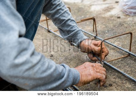 Labor is tying steel for construction site.