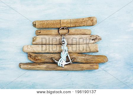 Decorative anchor with abstract driftwood design on beach sand background