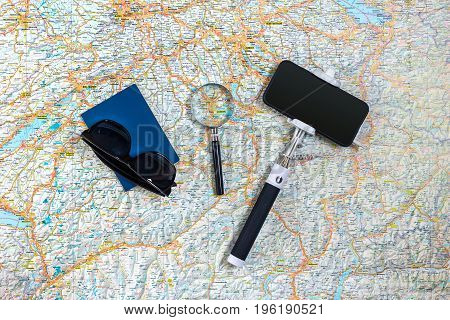 Travel accessories set on the map background: smart, passport and sunglasses. Top view point. Flat lay. Still life