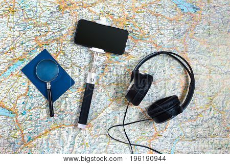 Travel accessories set on the map background: smart, headphones, passport and selfish stick. Top view point. Flat lay. Still life. Copy space
