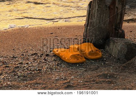 YellowOrange flipflop on the sandy beach sea water background at sunset. Resorts of the Krasnodar Territory Sea of Azov