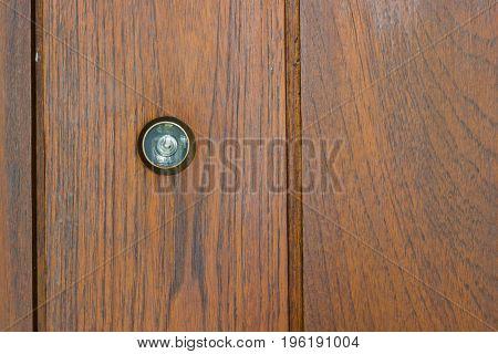 Peephole on the wooden door with copyspace