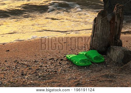 Summer vacation concept. green Flipflops on a sandy ocean beach. Wild uncomfortable beach. The sunset, the beach, the remains of the old pier.