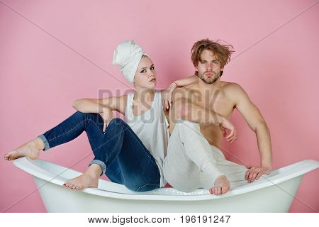man and woman with towel sitting on white bathtub on pink background family relationship and romance spa and beauty relax and hygiene healthcare couple in love