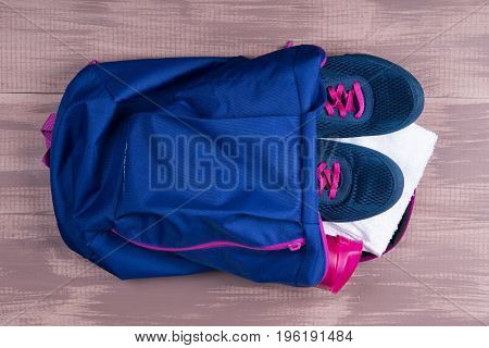 Collected backpack for doing sports lies on a wooden background
