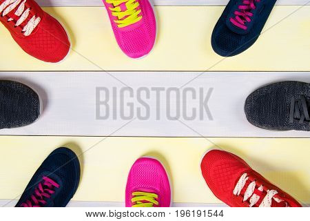 Scattered sports shoes on a multi-colored floor in the middle there is a place for inscriptions