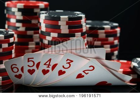 Straight flush against a black background behind a big bet on winning