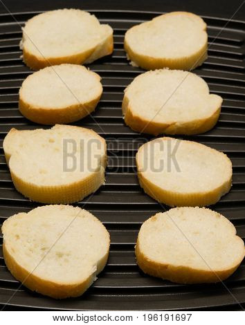 bread is cut into eight pieces and decomposed on a black background