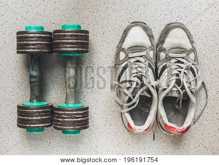 Vintage sport shoes and dumbbells on the floor top view. Sport background