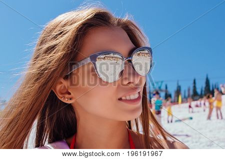 Close up portrait of a beautiful snowboard girl in bikini standing on the top of the snow mountain. Winner of a beauty contest.