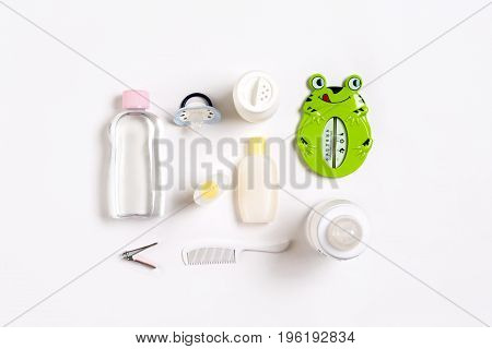 Hairbrush and cosmetics for newborns on a white background. Top view. Copy space. Still life. Flat lay