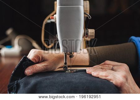 Vintage sewing machine and woman's hands sewing process