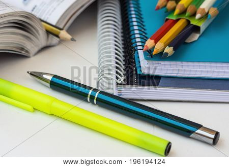 School supplies stationery multicolored pencils pen highlighter opened math workbook on white desktop learning studying college