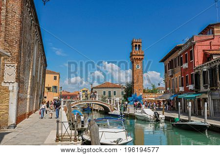 Murano, Italy - May 08, 2013. View of people, buildings and clock tower in front of canal at Murano, a nice little town on top of islands near Venice. Located in the Veneto region, northern Italy
