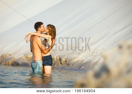 Beach lovers on romantic travel honeymoon vacation summer holidays romance. Young cute girl and man kissing and embracing on water
