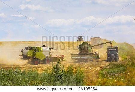 Combine harvester in action on wheat field. Palouse harvest season. Focus on green combine!