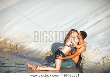 happy romantic lovers in travel honeymoon vacation summer holidays romance. in love girl and man kissing on ocean shore