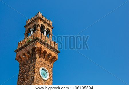 Detail of clock tower made of bricks with sunny blue sky in the background at Murano, a small and pleasant town on top of islands near Venice. Located in the Veneto region, northern Italy