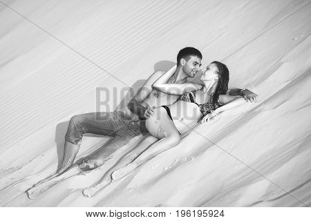 Lovers lying on the sand. romantic travel honeymoon vacation summer holidays. young girl dressed in a colorful dress and man in a violet t-shirt. they embracing outdoors. black and white photo
