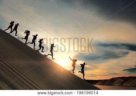 Silhouette of people running from high mountaine over sunset background. concept of playful, emotion, joy, game