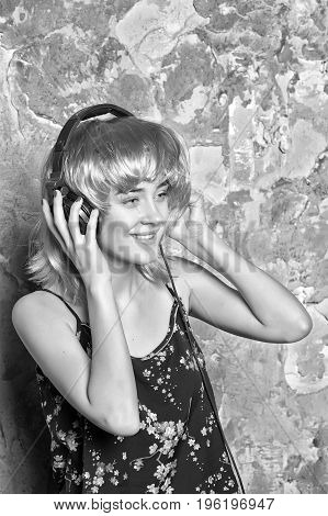 Hairdresser salon and barbershop. Girl smiling with artificial hair in headset. Beauty and fashion. Music dj and party. Woman in wig with music headphones black and white