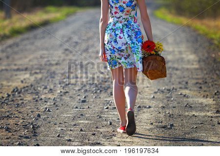 Girl in a dress.Summer.Romantic outing.Girl walking along the road with a basket of flowers.