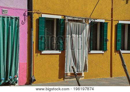 Burano, Italy - May 08, 2013. Close-up of windows on colorful walls and door with cloth on sunny day in Burano, a gracious little town full of canals, near Venice. In the Veneto region, northern Italy