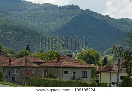 Scene with mountain glade, forest and residential district of bulgarian village Dushantsi, Central Balkan mountain, Stara Planina, Bulgaria