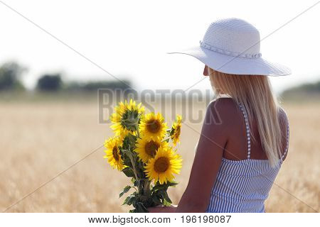 Young Beautiful Woman With A Hat In A Field With Dry Grass