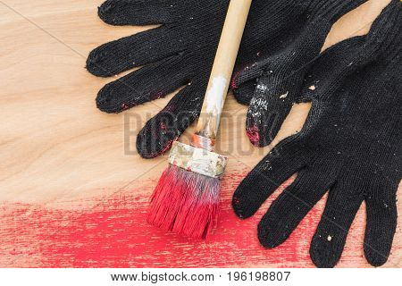 Black Gloves Stained In Paint, A Brush In Red Paint, Lie On Plywood