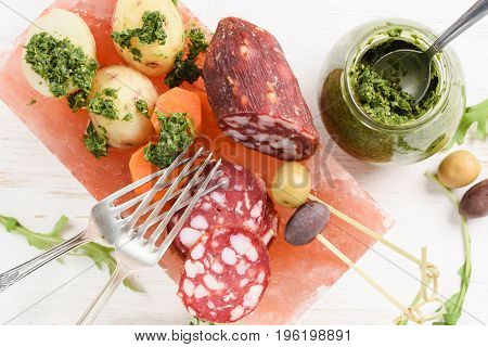 Salt block cooking. Smoked salami potatoes carrots arugula green and calamata olives with green chimichurri sauce on white background above view