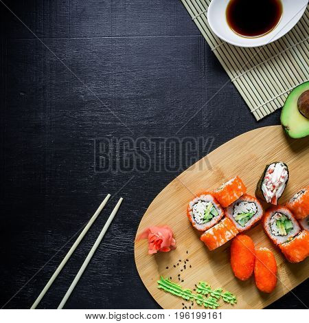 Asian food frame. Set of traditional japanese food on a black background. Sushi, avocado. Top view. Flat lay