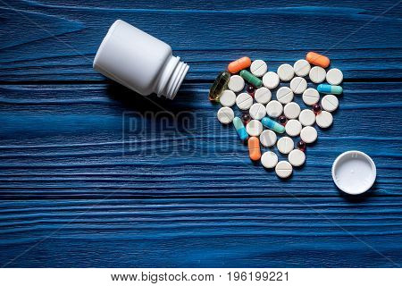 Heart made of pills and pill bottle on blue wooden table background top view.
