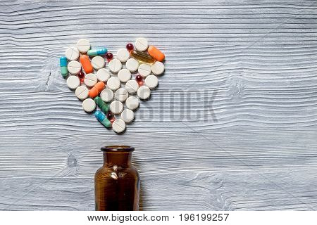 Pills and pill bottle on grey table background.