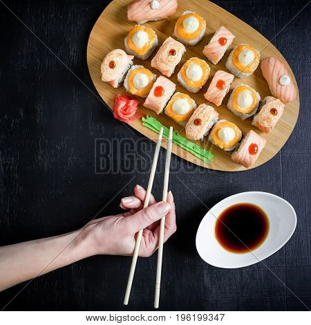 Sushi rolls, sauce and woman hand with chopsticks on black background. Traditional Japanese food. Flat lay. Top view.