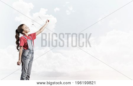 Cute kid girl in overalss with paper plane in hand