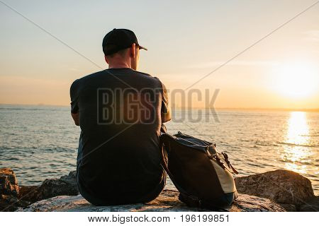 A tourist with a backpack on the coast. Travel, tourism. On the Sunset.