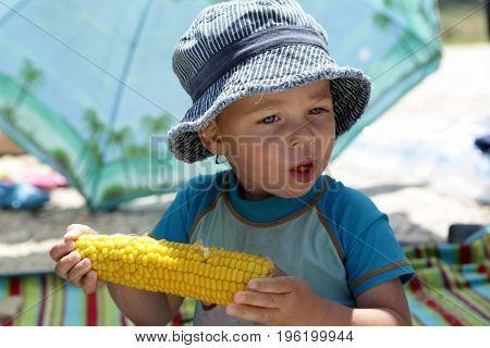 Child in panama eating corn on picnic