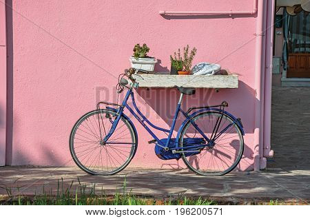 Close-up of bicycle leaning against colorful wall on a sunny day in Burano, a gracious little town full of canals, near Venice. Located in the Veneto region, northern Italy