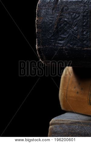 Old book with worn out hardcovers isolated on the black background.