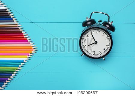 Wooden desk with colorful pencils Alarm clock and apple. Conceptual background in the style of Back to School