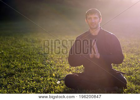 The ninja in black kimono is relaxing outdoors in nature.