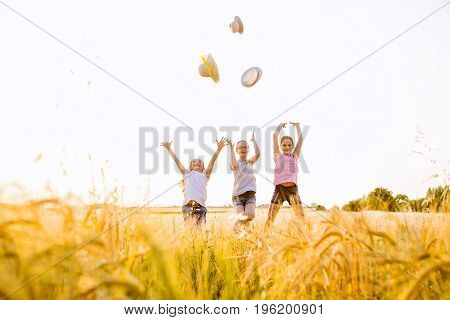Tree young girls jumping up in the field throwing straw hats in the air,wearing casual summer clothes.