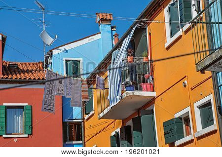 View of colorful terraced houses, balcony and clothes hanging in an alley on sunny day in Burano, a gracious little town full of canals, near Venice. Located in the Veneto region, northern Italy