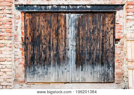 The old garage door in dirty scratch brick wall.