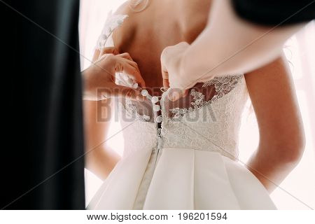 Bridesmaid helps fasten a wedding dress the bride before the ceremony. Wedding concept. Back view, close-up