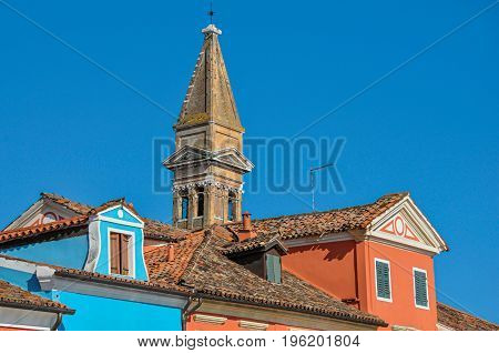 Close-up of colorful buildings, bell tower and rooftops in a blue sunny day at Burano, a gracious little town full of canals, near Venice. Located in the Veneto region, northern Italy