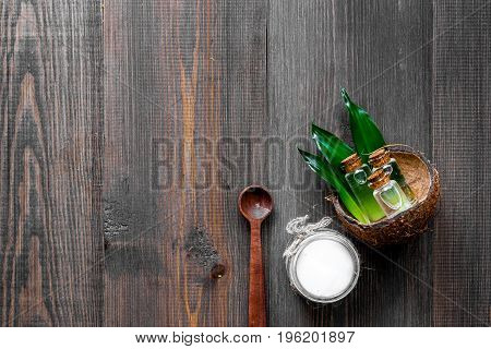 Skin care. Coconut cosmetics on wooden background top view.