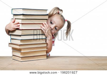 Little girl peeks out from behind a pile of books standing on a wooden table, isolated on a white background