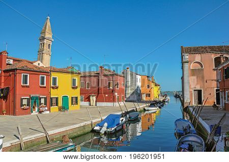 Overview of colorful buildings, bell tower and boats in blue sunny day, facing a canal at Burano, a gracious little town full of canals, near Venice. Located in the Veneto region, northern Italy